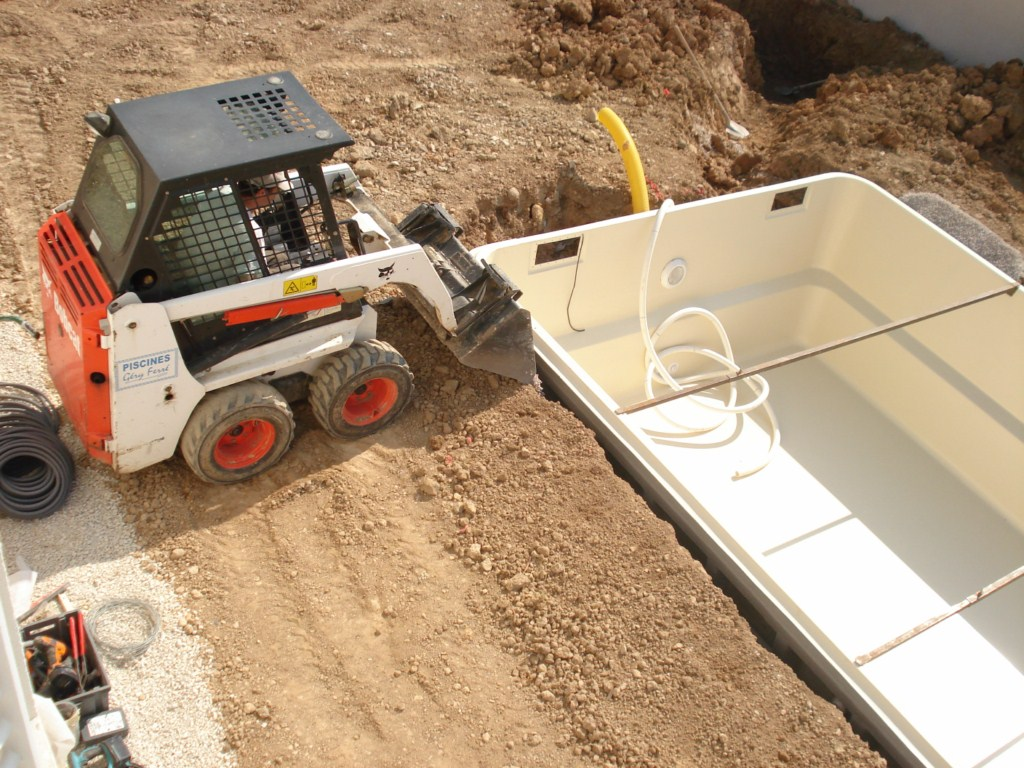 Remblaiement de la piscine en coque polyester France Piscines Composites et passage des canalisations.